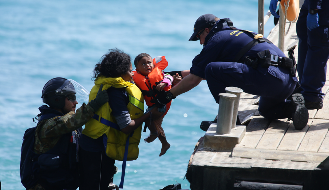 Asylum seekers at Flying Fish Cove Christmas Island are transferred to the jetty by crew from the HMAS Maryborough and Australian Customs and Border Protection Service after their boat crashed onto cliffs.