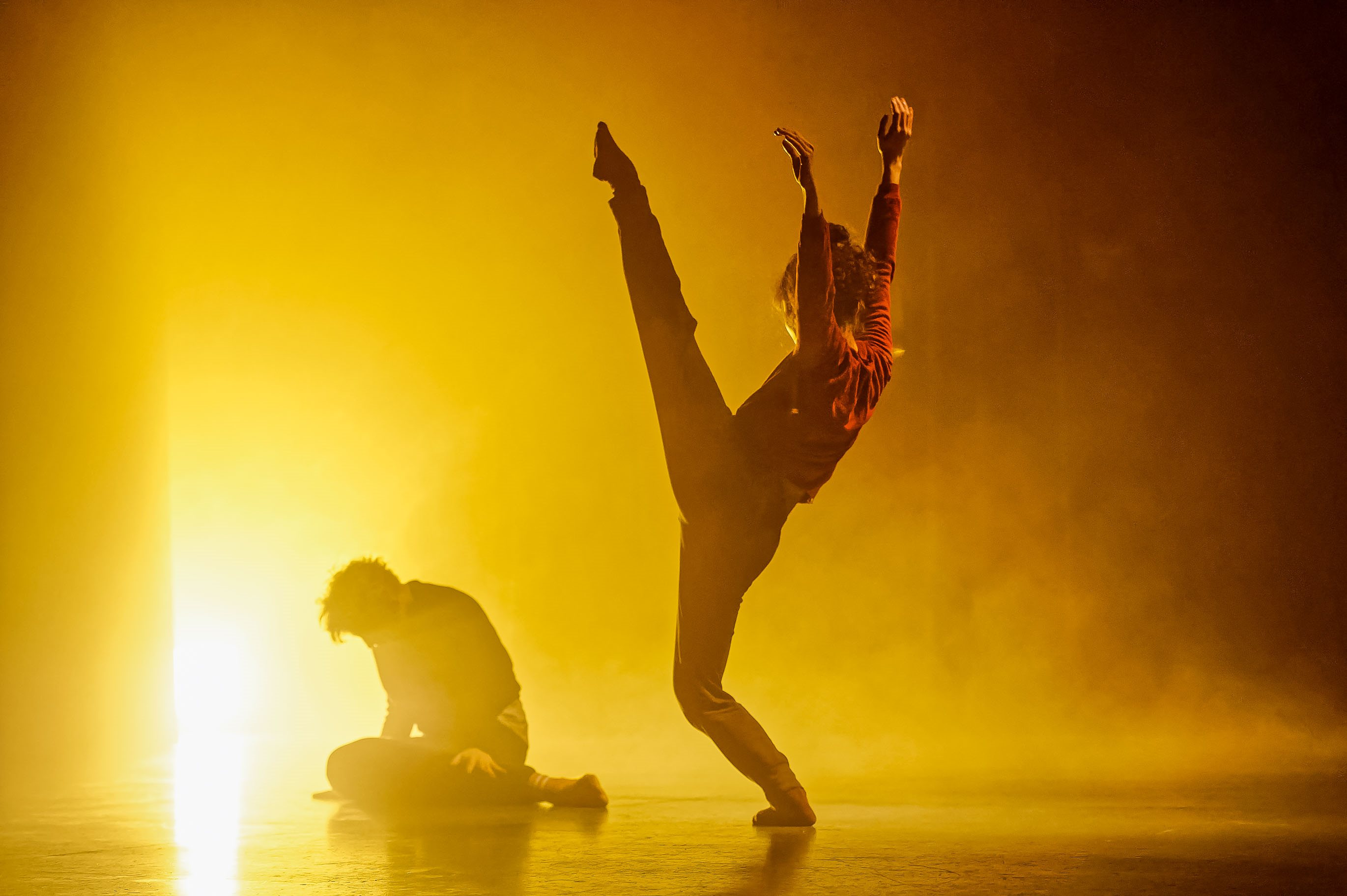 A dancer doing a kick and another dancer on the floor, in front of a yellow light