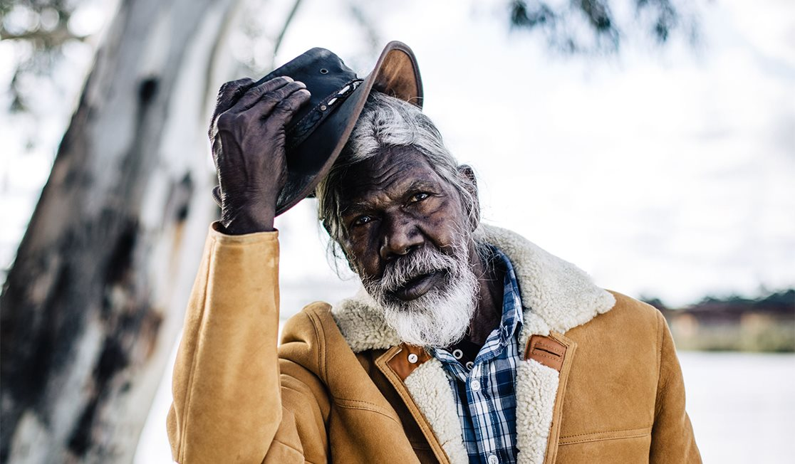 An older David Gulpilil, looking into the camera and removing a leather Akubra style hat